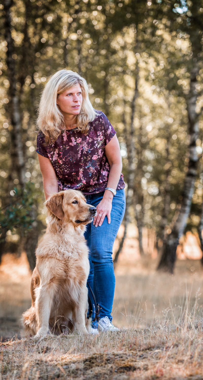 Frau steht mit ihrem Hund auf einer Wiese und streichelt ihn am Kopf