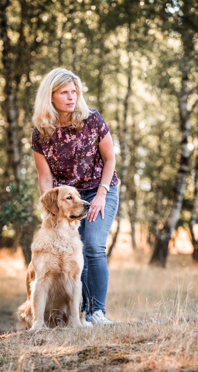 Frau steht mit ihrem Hund auf einer Wiese
